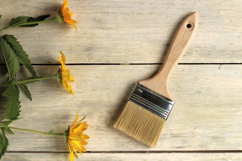 En målarfärgborste är bredvid härliga orange blommor på en träplankatabell för gammal vit tappning St?lle f?r text eller logo arkivfoton