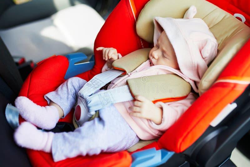 En månad behandla som ett barn att sova i bilsäte royaltyfria foton