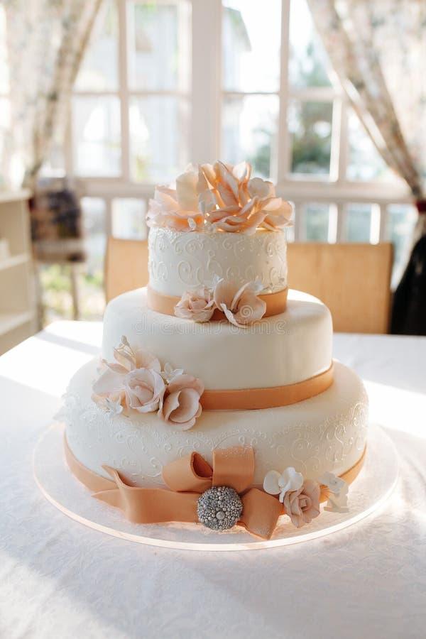 En mång- jämn vit bröllopstårta på den vita tabellen och rosa färger blommar överst arkivfoton