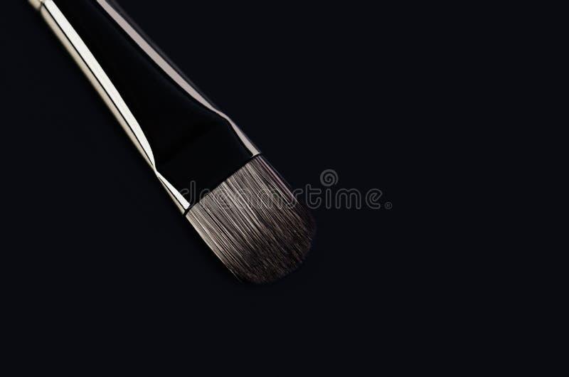 En makeupborstenärbild diagonalt på en svart bakgrund Hori fotografering för bildbyråer