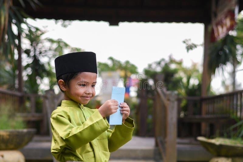 En malajiska pojke i den malajiska traditionella torkduken som visar hans lyckliga reaktion efter mottaget pengarfack under Eid F royaltyfria bilder
