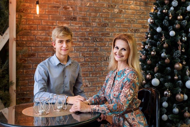 En mamma och en son sitter vid ett bord i ett kafé som är dekorerat med en julgran royaltyfri fotografi