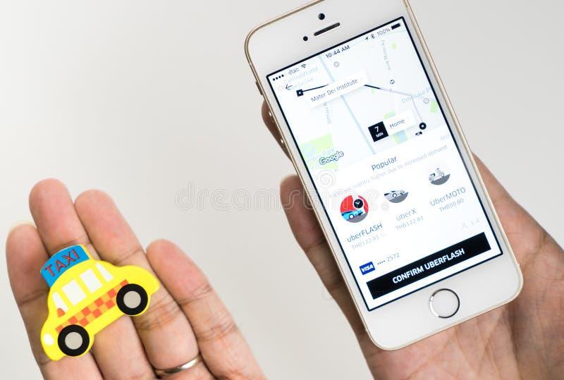 En man är den hållande taxien och Uber app som försöker att göra ett val royaltyfri fotografi