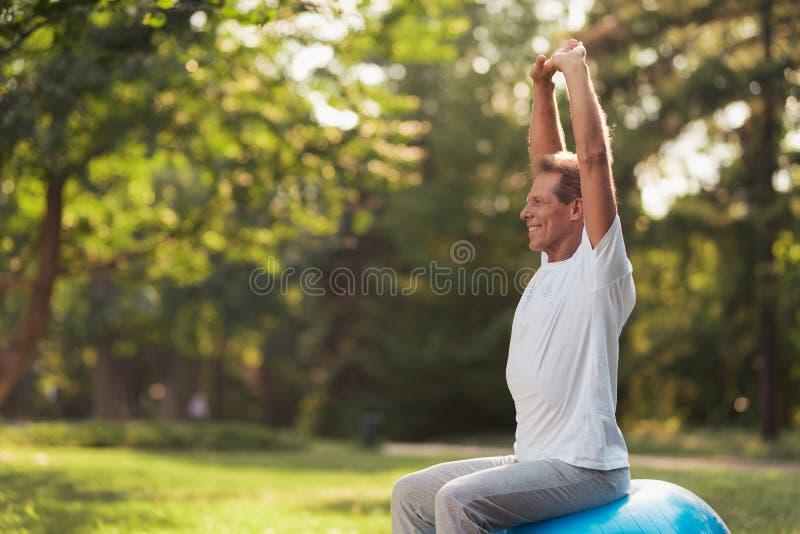 En man är förlovad i en yoga parkerar med en blå yogaboll Han sitter på bollen som lyfter upp hans händer royaltyfria foton