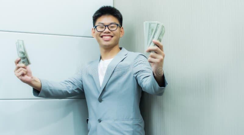En man är jätteglad att rymma sedlar i hans hand royaltyfri bild