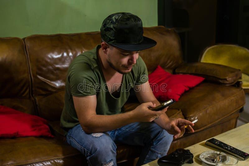 En man är röka och tala på telefonen arkivbild