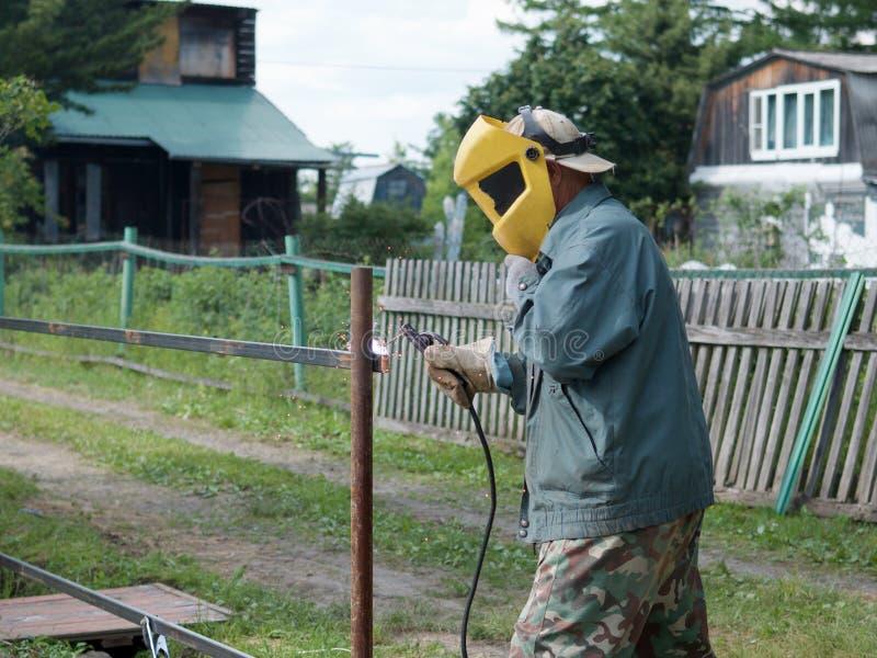 En man arbetar med en svetsningsmaskin i trädgården royaltyfri fotografi