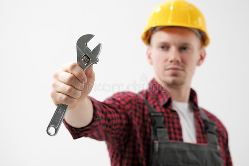 En man, en arbetare, i en gul hjälm, i funktionsdugliga overaller och en röd rutig skjorta, rymmer ett stål justerbart arkivbilder