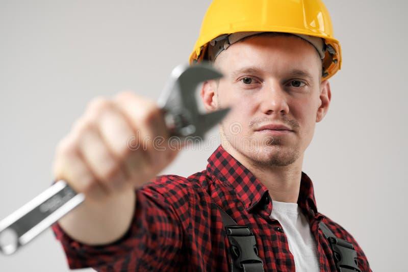 En man, en arbetare, i en gul hjälm, i funktionsdugliga overaller och en röd rutig skjorta, rymmer ett stål justerbart royaltyfri bild