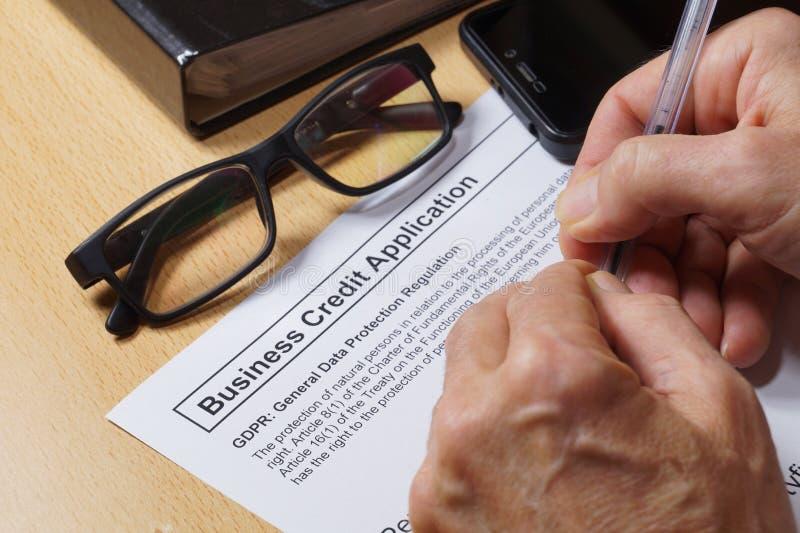 En man avslutar en krediteringsform med en sats för reglering för skydd för GDPR-general data Affärskrediteringsapplikation arkivfoton