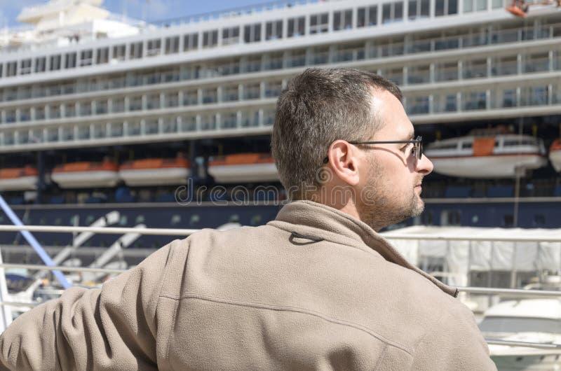 En man bakifrån i en hamn arkivfoto