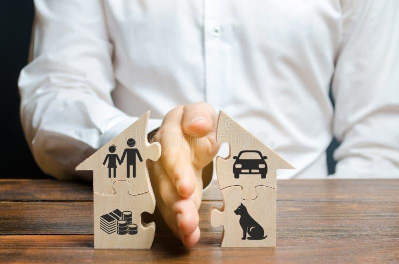 En man delar ett hus med hans gömma i handflatan med bilder av egenskapen, barn och husdjur Skilsmässabegrepp, egenskapsuppdelnin royaltyfri foto