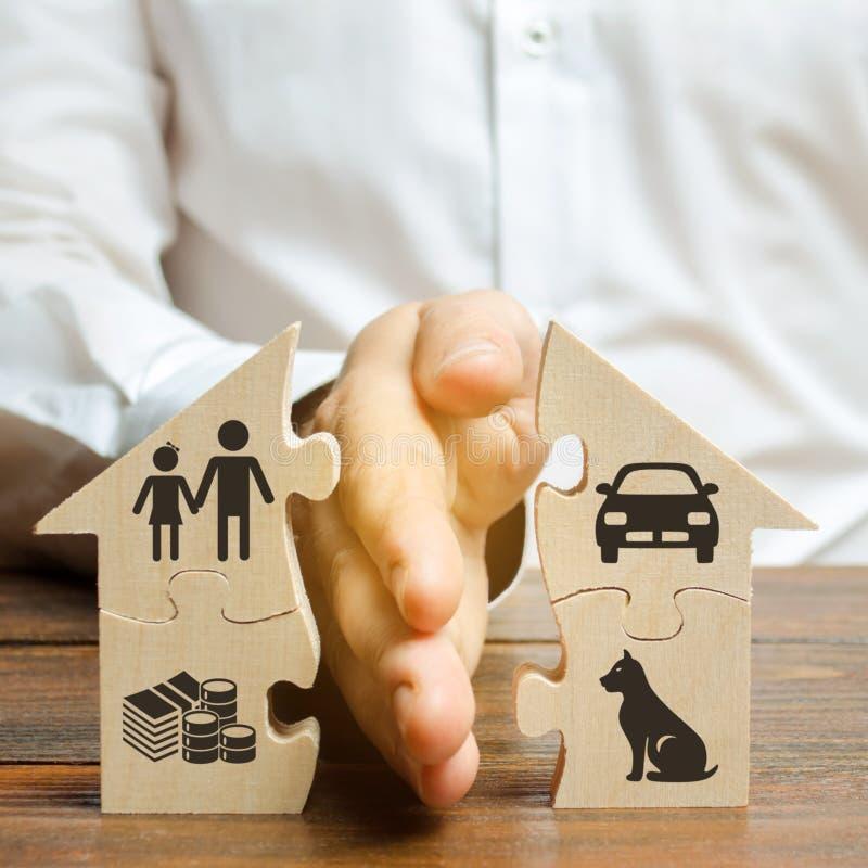 En man delar ett hus med hans g?mma i handflatan med bilder av egenskapen, barn och husdjur Skilsm?ssabegrepp, egenskapsuppdelnin royaltyfria bilder