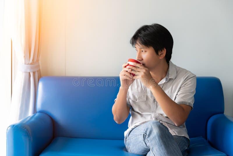 En man dricker kaffe i morgonen, medan sitta på den blåa soffan Han ser yttersidan och tänker för att finna idérika idéer arkivfoto