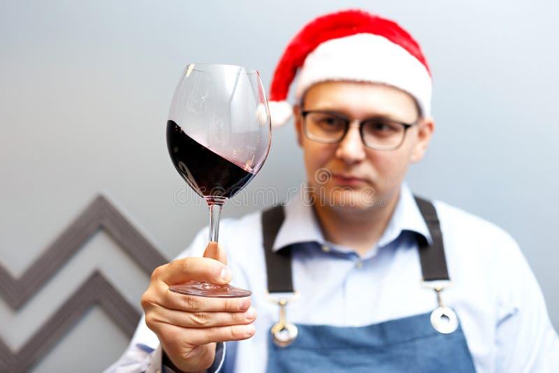 En man dricker vin i en santa hatt arkivfoto