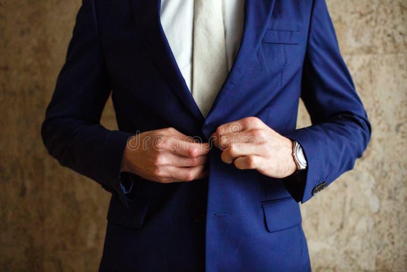 En man fäster det blåa omslaget för knappar på hans hand hans klocka arkivbilder