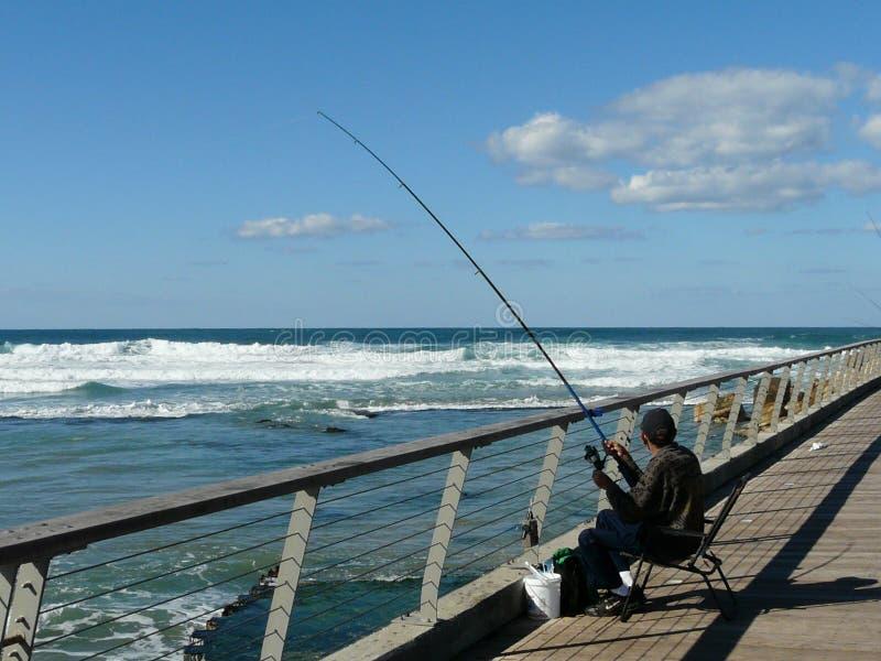 En man fångar fisken att sitta på promenaden av Tel Aviv royaltyfri fotografi