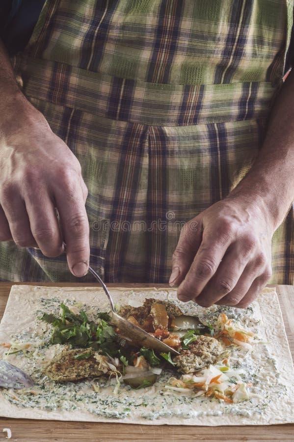 En man förbereder en rulle med ost och grönsaker på tabellen royaltyfria bilder
