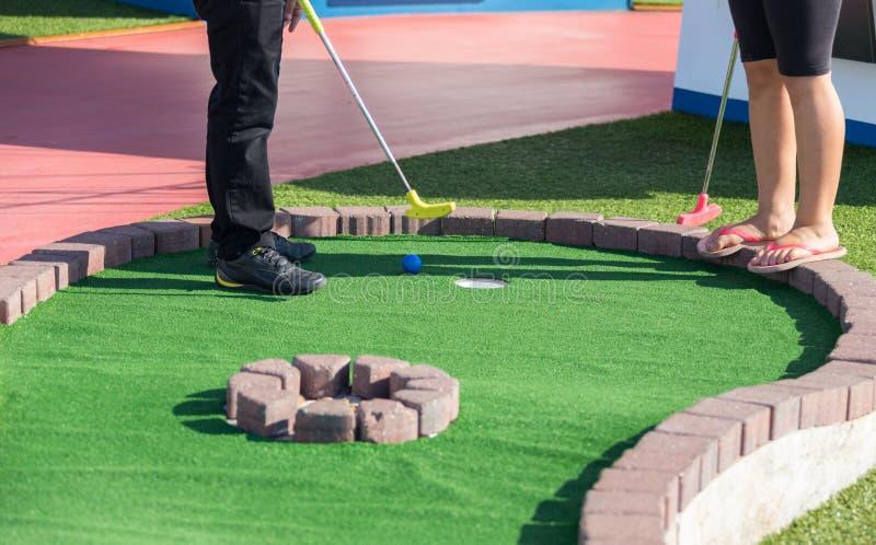En man förbereder sig att slå en boll under den mini- golfleken arkivbilder