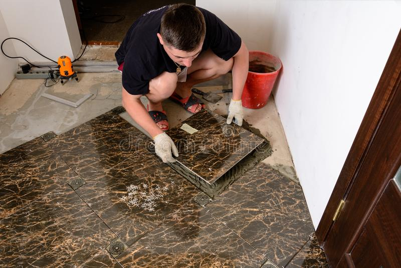 En man förlägger en keramisk tegelplatta under tryck över ett lim i rum av brun färg arkivbilder
