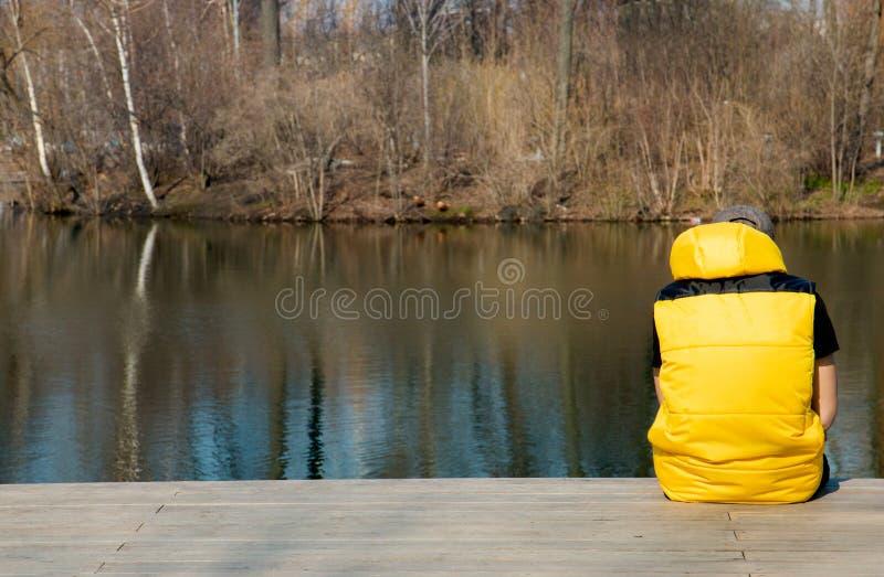 En man från baksidan i ett gult västsammanträde på en plattform nära dammet arkivbilder