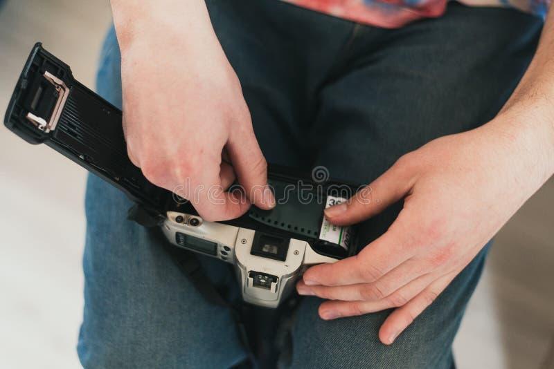 En man fyller kamerafilmen satt film i kameran sätt bandet i maskinen royaltyfri bild