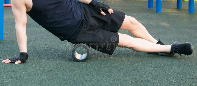 En man går in för sportar utomhus och att knåda ett lår med en massagerulle, närbilden arkivbilder