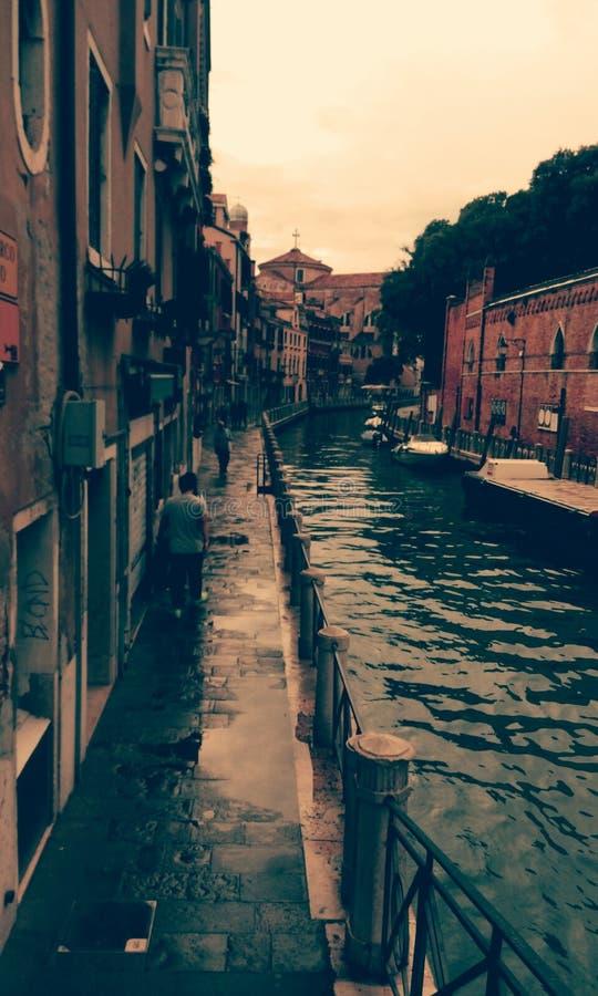 En man går en longside den härliga kanalen av Venedig på ett smalt gå område bredvid en gammal byggnad, når han har regnat arkivfoton