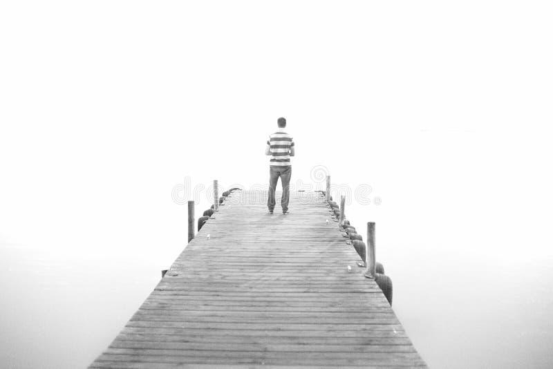 En man går på träpir i hög tangent svart white royaltyfri bild