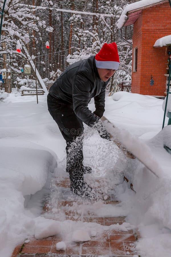 En man gör ren moment från snö I en röd hatt av Santa Claus och ett svart omslag för läder I filtkängor Göra klar snö från backya arkivfoton