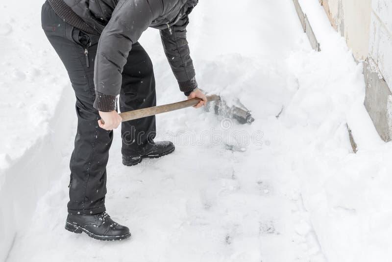 En man gör ren snöskyffeln nära huset arkivbild