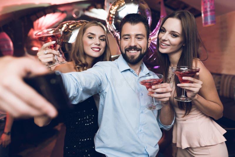 En man gör selfie med hans vänner Han har gyckel i en nattklubb Mot bakgrundsställningen hans vänner med coctailar royaltyfri bild