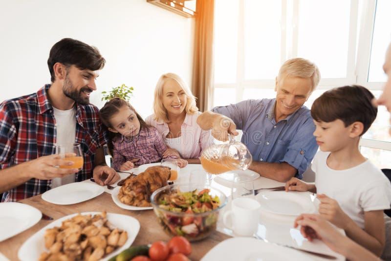 En man häller fruktsaft för hans familj, som samlade på en festlig tabell för tacksägelse royaltyfri bild