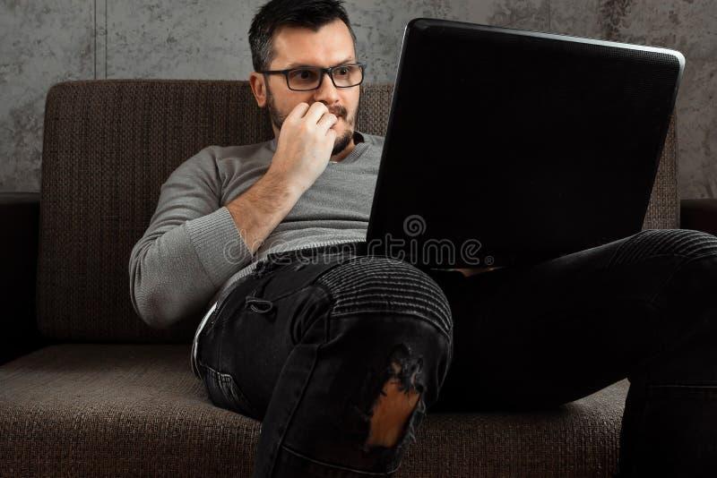 En man h?ller ?gonen p? en vuxen video p? en b?rbar dator, medan sitta p? soffan Begreppet av pornografi, m?ns behov, pervers man royaltyfri fotografi