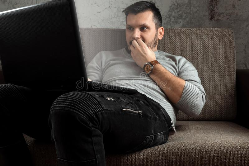 En man h?ller ?gonen p? en vuxen video p? en b?rbar dator, medan sitta p? soffan Begreppet av pornografi, m?ns behov, pervers man arkivbilder