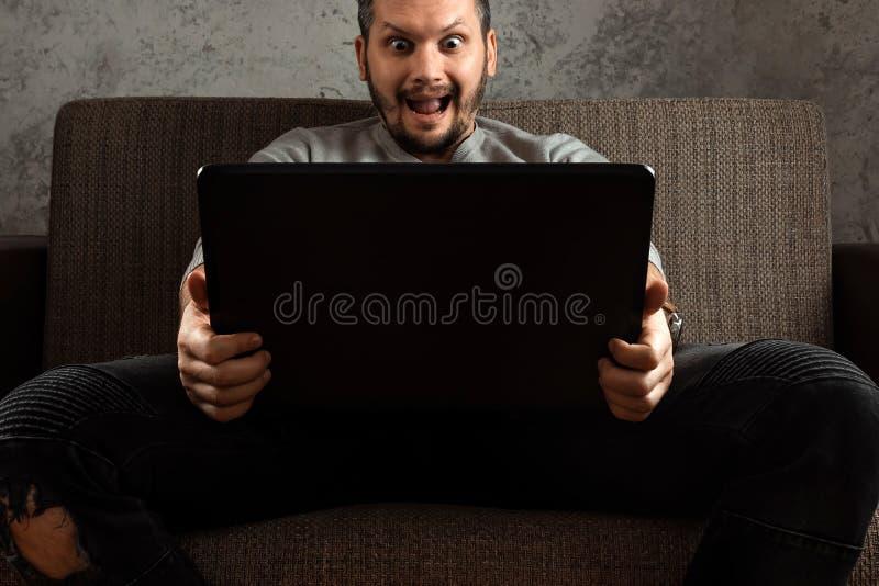 En man h?ller ?gonen p? en vuxen video p? en b?rbar dator, medan sitta p? soffan Begreppet av pornografi, m?ns behov, pervers man fotografering för bildbyråer