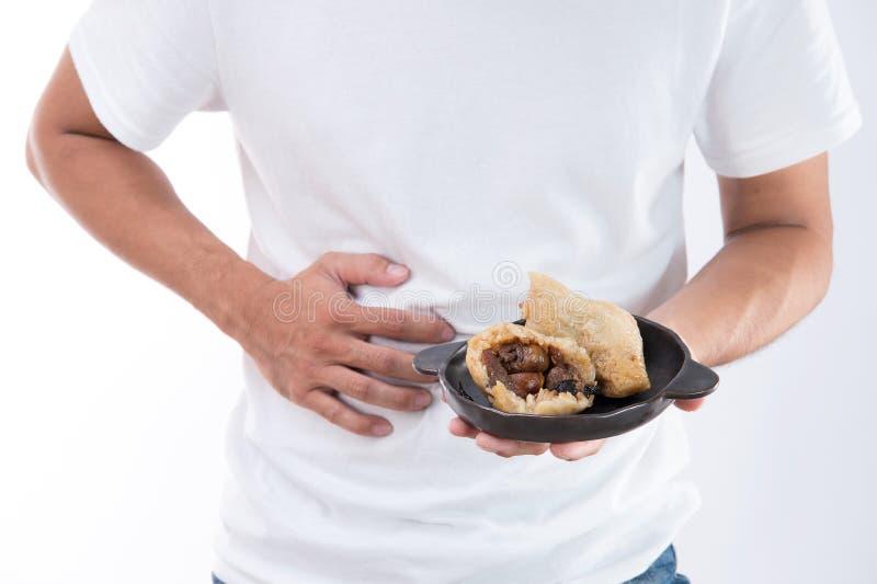 En man har ett magknip, når han har ätit den läckra zongziriceklimpen på Dragon Boat Festival, asiatisk traditionell mat royaltyfria foton
