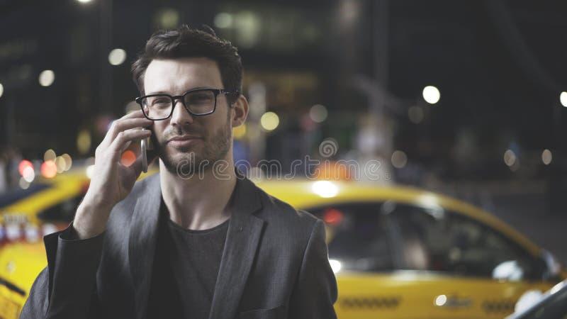 En man har en nattappell på gatan royaltyfri foto