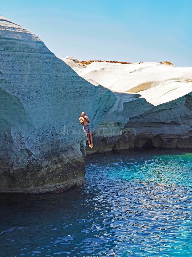 En man hoppar från klippan nära den Sarakiniko stranden i Milos i de Cyclades öarna av Grekland royaltyfri fotografi