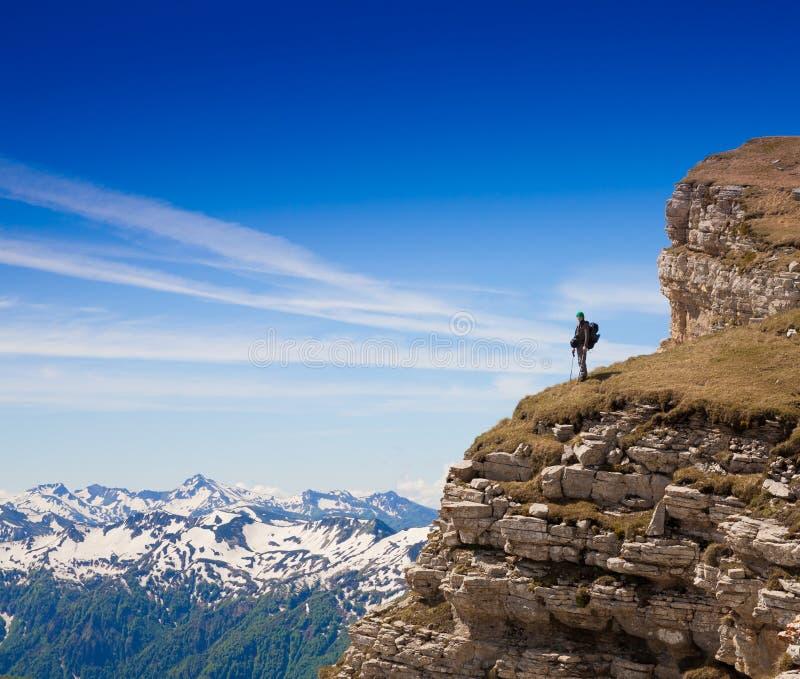 En man i bergdagsommar Stenig rutt blå sky arkivbild
