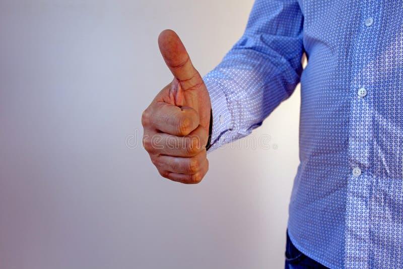 En man i en blå skjorta och jeans visar gesten av godkännande royaltyfri bild