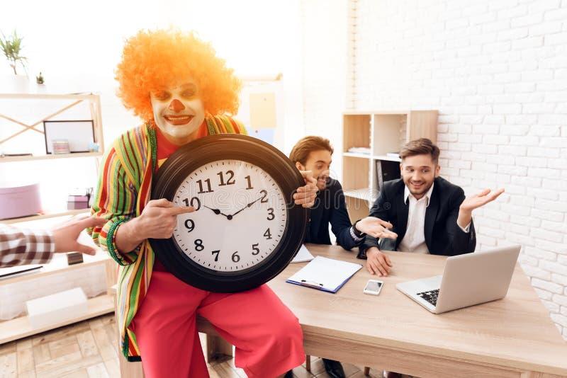En man i en clowndräkt står bredvid män i affärsdräkter, som sitter på skrivbordet arkivbild