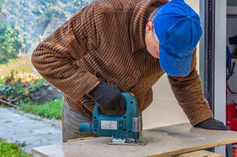 En man i de svarta funktionsdugliga handskarna och ett brunt omslag och en blå hatt klipper ett bräde som använder ett figursågma arkivfoton
