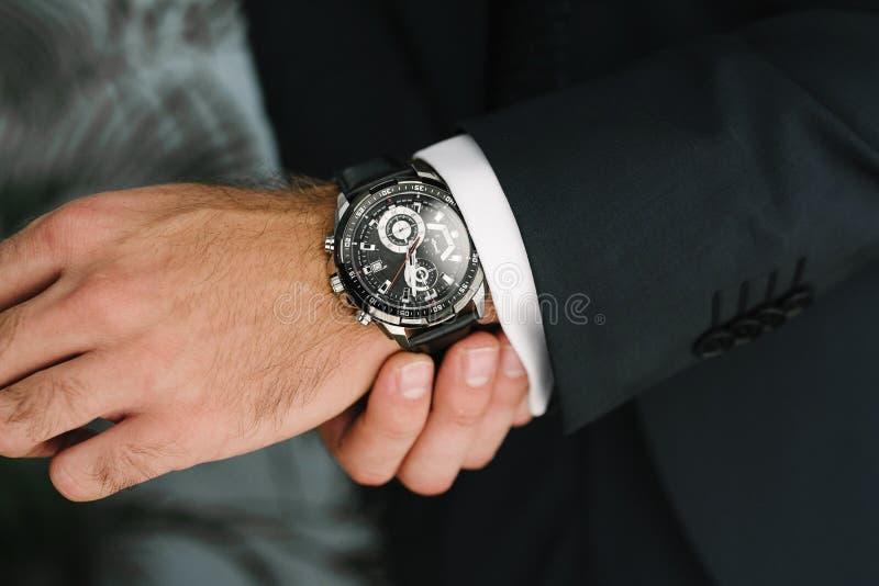 En man i en dr?kt justerar upp klockan p? hans handslut royaltyfri foto