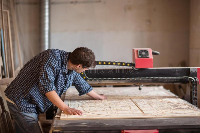 En man i en carpenter& x27; s shoppar med en stor CNC-maskin, livsstil, royaltyfria foton