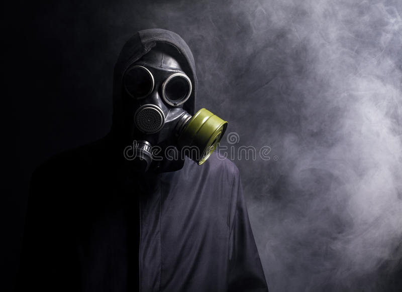 En man i en gasmask i röken arkivbilder
