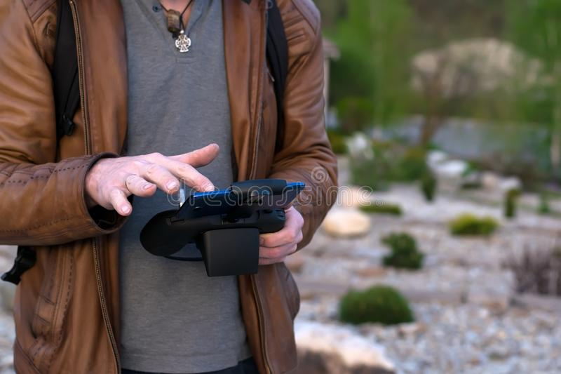 En man, i ett läderomslag kontrollerar apparaten från fjärrkontrollen royaltyfri foto