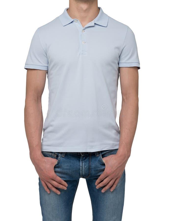 En man i ett ljus - den blåa poloskjortan och grov bomullstvill rymmer hans händer i fack arkivbild