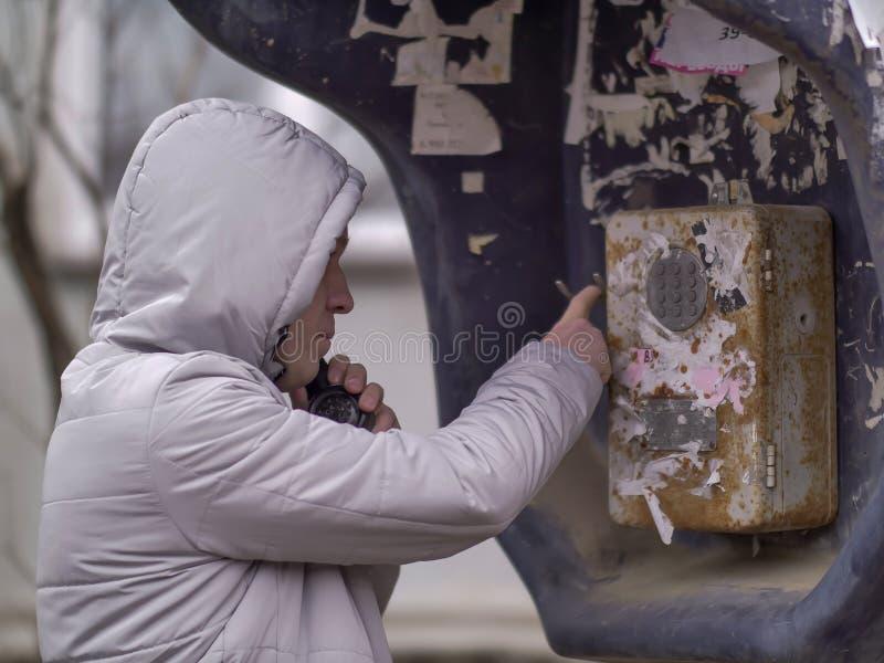En man i ett ljust omslag i huven kallar en gammal payphone arkivfoton