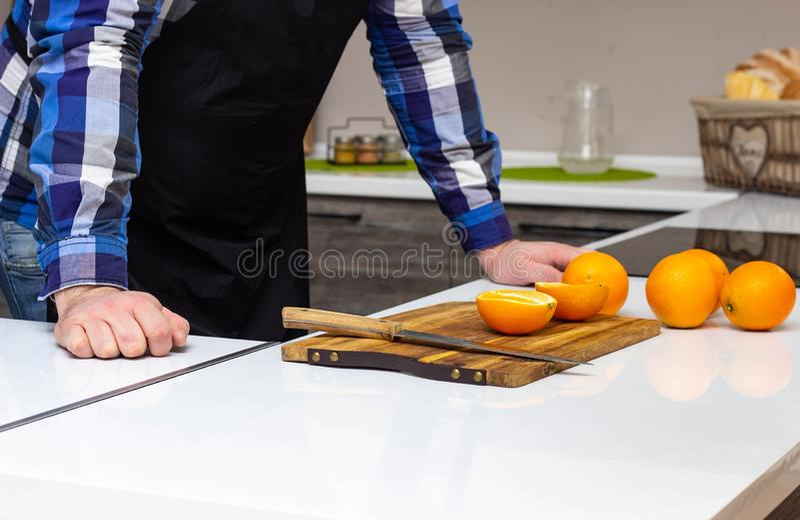 En man i ett modernt kök klipper saftiga fruktapelsiner, en sund livsstil arkivfoto